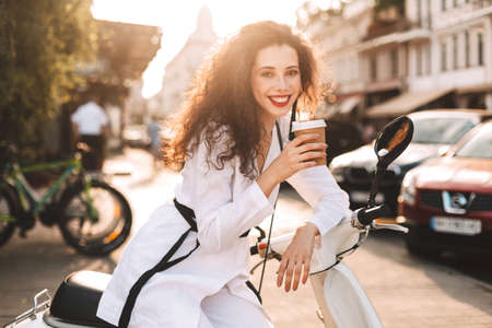 Young smiling lady with dark curly hair in white costume sitting on white moped with cup of coffee to go, and happily looking in camera with city view on background