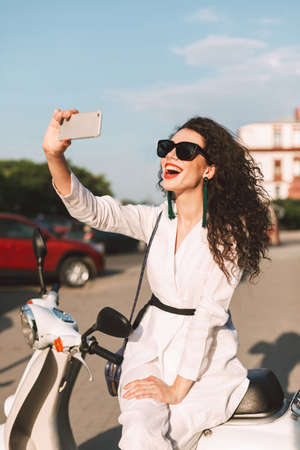 Young cheerful woman with dark curly hair in white costume and sunglasses sitting on white moped, and happily taking photos on cellphone frontal camera while spending time on city street