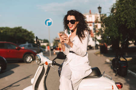 Joyful lady with dark curly hair in white costume and sunglasses sitting on white moped and happily using her cellphone on street with city view on background.