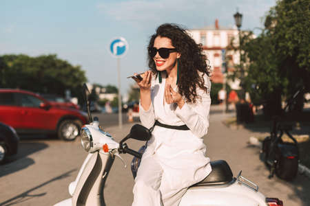 Young woman with dark curly hair in white costume and sunglasses sitting on white moped, and emotionaly exlaining something while talking on her cellphone on street with city view on background