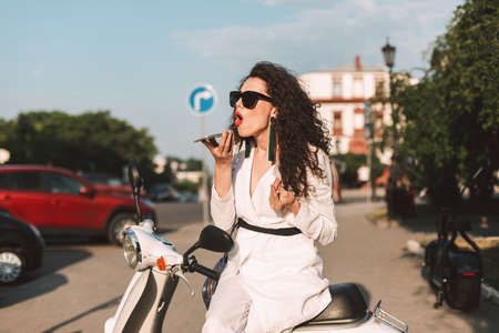 Young woman with dark curly hair in white costume and sunglasses sitting on white moped and emotionalytalking on her cellphone on street with city view on background.
