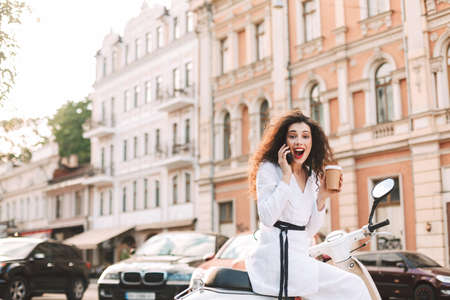 Cheerful lady with dark curly hair in white costume sitting on white moped with cup of coffee to go, and happily looking in camera while talking on cellphone with city view on background