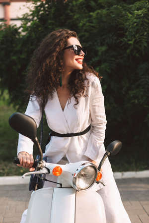 Beautiful smiling lady with dark curly hair in white costume and sunglasses sitting on white moped, and happily looking aside on street