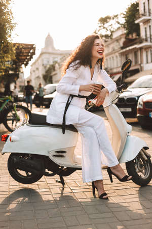 Pretty lady with dark curly hair in white costume sitting on white moped with cup of coffee to go, and happily laughing with city view on background