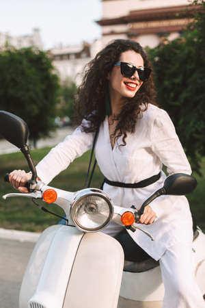 Pretty smiling woman with dark curly hair in white costume and sunglasses sitting on white moped, and joyfully looking aside on street