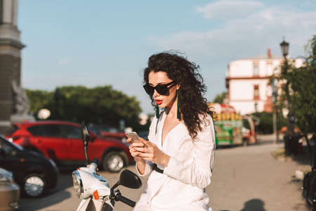 Beautiful lady with dark curly hair in white costume and sunglasses sitting on white moped, and thoughtfully using her cellphone while spending time on city street