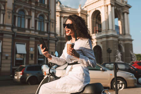 Young joyful woman with dark curly hair in sunglasses and white costume sitting on moped with cup of coffee to go, and happily using her cellphone with city view on background Фото со стока