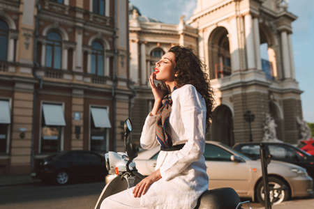 Young beautiful woman with dark curly hair in white costume sitting on moped, and dreamily closing her eyes with city view on background Фото со стока