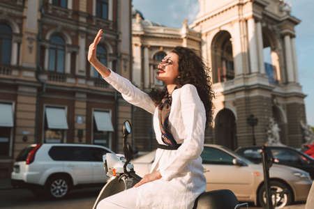 Pretty smiling woman with dark curly hair in white costume sitting on moped and happily covering her face with hand from sunlights with city view on background. Фото со стока