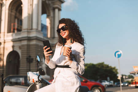 Happy smiling lady with dark curly hair in sunglasses and white costume sitting on white moped with cup of coffee to go, and cellphone in hand with city view on background