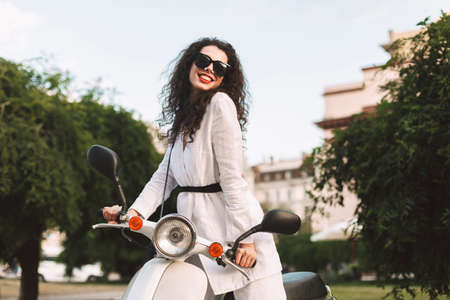 Young smiling woman with dark curly hair in white costume and sunglasses sitting on white moped, and happily looking in camera on street Фото со стока