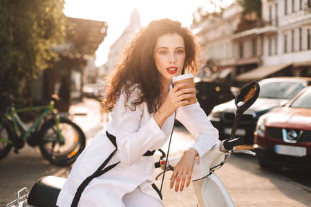 Young lady with dark curly hair in white costume sitting on white moped with cup of coffee to go, and dreamily looking in camera with beautiful city view on background Фото со стока