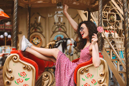 Cheerful lady with dark curly hair in sunglasses and dress holding lolly pop candy in hand and riding on carousel while spending time in amusement park.