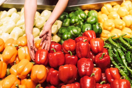 Close up stand with variety of fresh peppers in modern supermarket Stock Photo