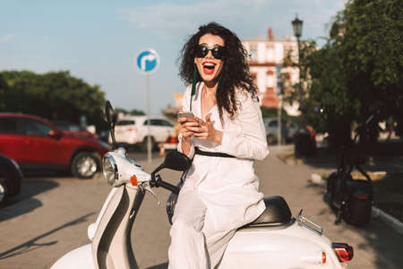 Cheerful lady with dark curly hair in white costume and sunglasses sitting on white moped with cellphone in hands, and happily looking in camera on street with city view on background Фото со стока