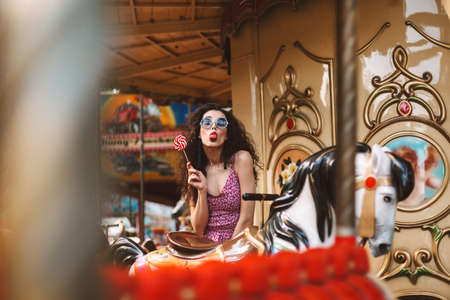 Young cool lady with dark curly hair in sunglasses and dress showing tongue in camera while riding on carousel with lolly pop candy in hand in amusement park. Stok Fotoğraf