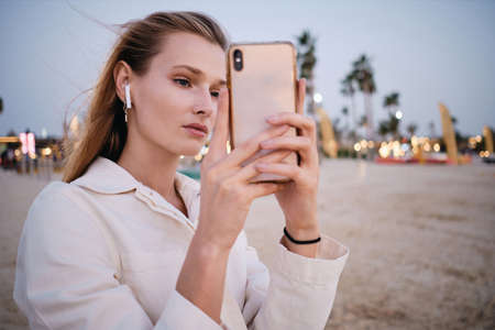 Young attractive woman with blond hair in wireless earphones thoughtfully taking photos on cellphone on beautiful beach alone