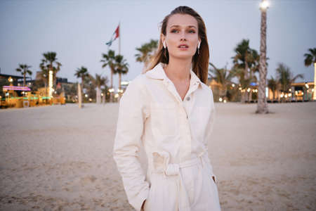 Young gorgeous woman with blond hair in wireless earphones and white denim overalls thoughtfully looking aside on beautiful beach alone