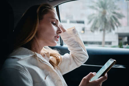 Young gorgeous woman with blond hair dreamily using cellphone riding in modern car alone