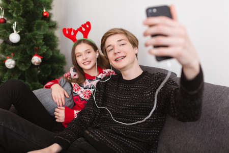 Young couple sitting on sofa at home in earphones and taking selfie while spending time together with Christmas tree on background.