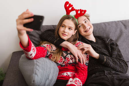 Portrait of young smiling couple sitting on sofa at home and taking funny selfie while spending time together.