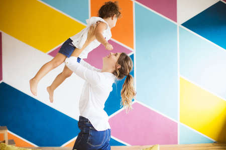 Young mother in white shirt joyfully lifting little pretty daughter up spending time together at home with colorful wall on background Banque d'images