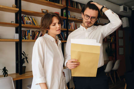 Young disappointed business colleagues thoughtfully reading envelope letter working together in modern office