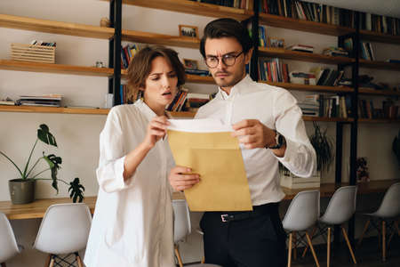 Young disappointed business colleagues standing thoughtfully reading envelope letter working together in modern office Фото со стока