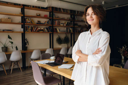 Young attractive woman in white shirt dreamily looking in camera with desk on background in modern office Stock fotó