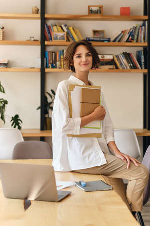Young attractive smiling woman in white shirt happily looking in camera sitting on desk with papers and laptop in modern office
