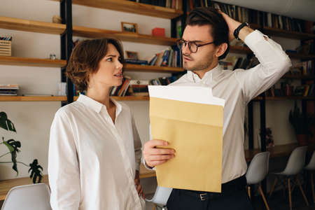 Young disappointed business colleagues standing with envelope letter sadly looking at each other in modern office