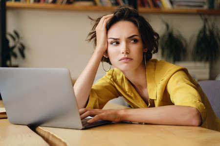 Portrait of young serious businesswoman sitting at the desk tiredly looking aside working on laptop in modern office