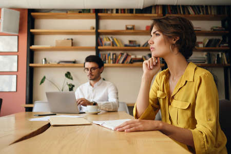 Side view of young woman sitting at the table with notepad thoughtfully working with colleague on background in modern office Фото со стока