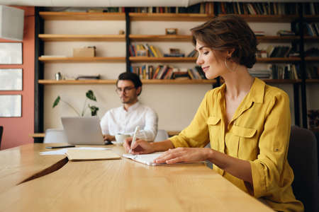 Young beautiful woman sitting at the table happily writing in notepad with colleague on background at work in modern office