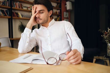 Young exhausted man sitting at the table with notepad and eyeglasses tiredly leaning head on hand at work in modern office