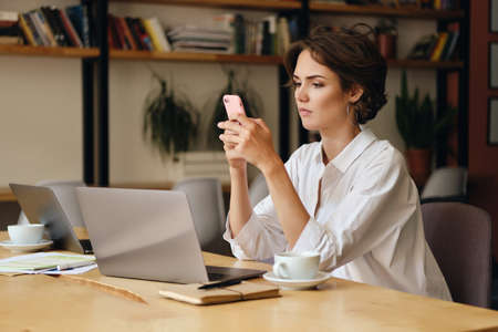 Young pensive woman sitting at the table with laptop and cup of coffee thoughtfully using cellphone in modern office