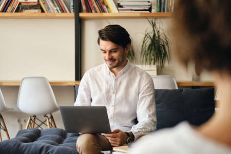 Young handsome smiling businessman sitting on sofa with colleague happily working on laptop in modern co-working space Фото со стока