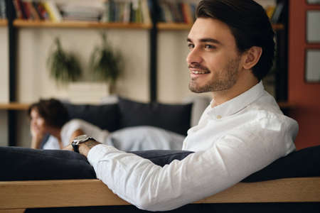 Young attractive smiling businessman sitting on sofa with colleague happily looking aside in modern co-working space