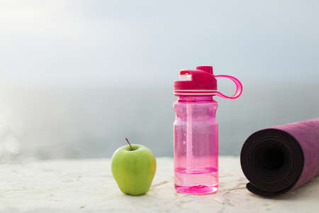 Close up green apple,pink sport bottle and yoga mat over fuzzy background 版權商用圖片