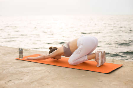Young woman dreamily practicing yoga with sport bottle near by the sea. Girl in sporty top and white leggings stretching on orange yoga mat with sea view on background