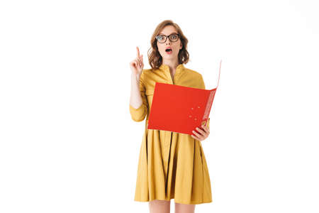 Portrait of pretty lady in eyeglasses and yellow dress holding red folder while amazedly looking in camera on white background isolated. Фото со стока