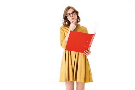Portrait of young lady in eyeglasses and yellow dress standing with red folder in hand, and thoughtfully looking aside on white background isolated Stock fotó