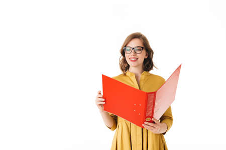 Portrait of young joyful lady in eyeglasses standing, and happily looking in open red folder on white background isolated