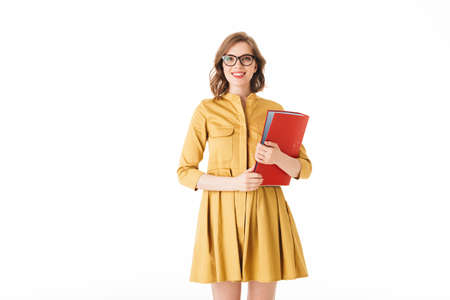 Portrait of beautiful smiling lady in eyeglasses and dress standing with red folder in hand and joyfully looking in camera on white background isolated