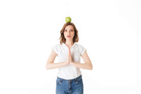 Portrait of young lady standing with green apple on head and amazedly looking in camera on white background isolated.