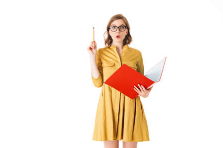 Portrait of young pretty lady in eyeglasses and yellow dress standing with red folder and pencil in hands, while amazedly looking in camera on white background isolated