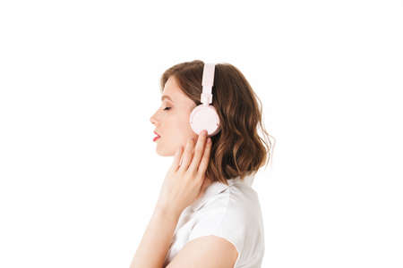 Portrait of beautiful lady listening music in headphones while dremily closing her eyes on white background isolated.