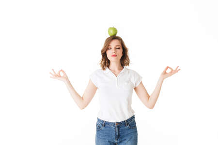 Portrait of young lady standing with green apple on head and meditating on white background isolated. Фото со стока