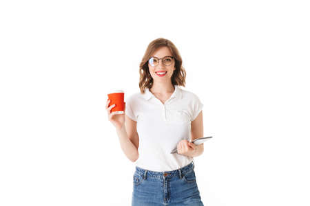 Portrait of young beautiful lady in eyeglasses standing with cup of coffee to go and the tablet in hands, while happily looking in camera on white background isolated Фото со стока
