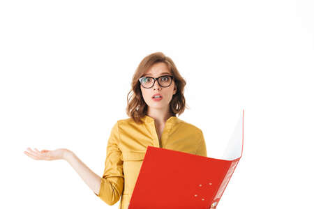 Portrait of young lady in eyeglasses standing with open red folder, and amazedly looking in camera on white background isolated Фото со стока